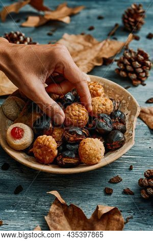 a young man takes a panellet, a typical confection of Catalonia, Spain, eaten traditionally in All Saints Day, from a plate with some more and a roasted sweet potato and some roasted chestnuts