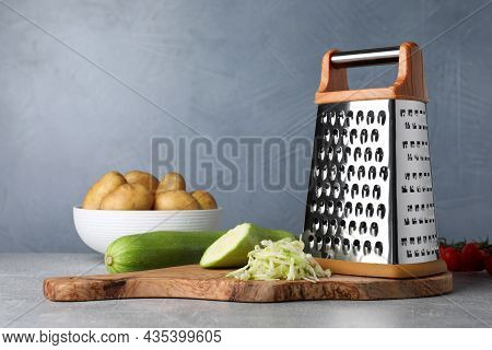 Grater, Fresh Zucchinis And Potatoes On Grey Table. Space For Text