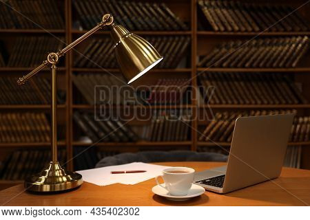 Lamp, Cup Of Drink And Laptop On Wooden Table Near Shelves With Collection Of Vintage Books In Libra