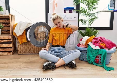 Young blonde woman doing laundry sitting by washing machine suffering of neck ache injury, touching neck with hand, muscular pain