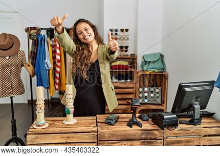 Beautiful hispanic woman working at fashion shop approving doing positive gesture with hand, thumbs up smiling and happy for success. winner gesture.