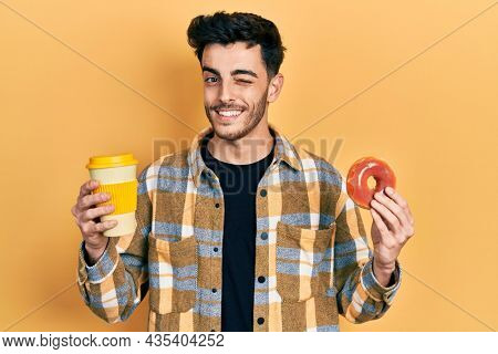 Young hispanic man eating doughnut and drinking coffee winking looking at the camera with sexy expression, cheerful and happy face.