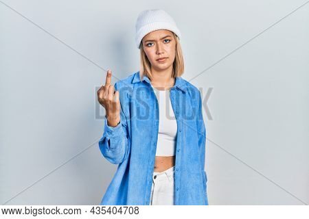 Beautiful blonde woman wearing wool hat showing middle finger, impolite and rude fuck off expression