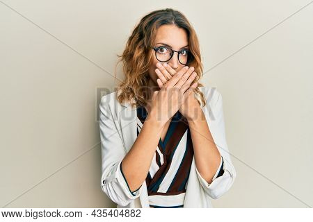 Young caucasian woman wearing business style and glasses shocked covering mouth with hands for mistake. secret concept.