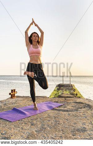 Woman Practicing Yoga, Doing Vrikshasana Exercise, Tree Pose With Namaste, Standing On The Pier On A