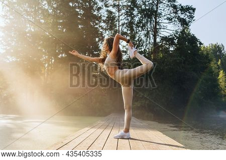 A Woman Practicing Yoga, Performs The Natarajasana Exercise, The Pose Of The King Of Dancers With An