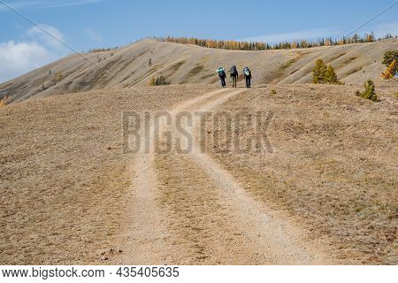A Group Of Tourists Walk Up A Winding Mountain Road To The Top Of The Ridge. Active Rest With Family