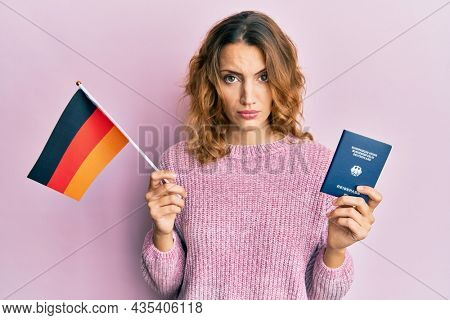 Young caucasian woman holding germany flag and passport skeptic and nervous, frowning upset because of problem. negative person.