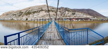 A Panoramic View Of The Sturdy Wooden Suspension Bridge Over A Wide And Calm River Goes To The Mount