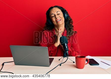Beautiful middle age woman working at radio studio begging and praying with hands together with hope expression on face very emotional and worried. begging.