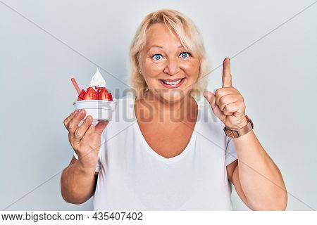 Middle age blonde woman eating strawberry ice cream smiling with an idea or question pointing finger with happy face, number one