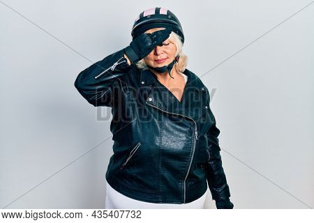 Middle age blonde woman holding motorcycle helmet tired rubbing nose and eyes feeling fatigue and headache. stress and frustration concept.