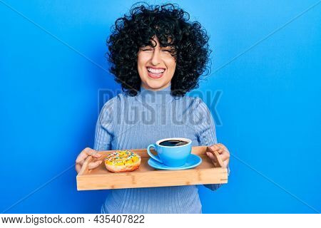 Young middle east woman holding tray with doughnut and cup of coffee winking looking at the camera with sexy expression, cheerful and happy face.
