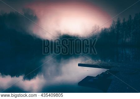 Small lake in enchanted forest in magic, mysterious fog at night. Halloween background