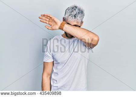 Young hispanic man with modern dyed hair wearing white t shirt and glasses covering eyes with arm, looking serious and sad. sightless, hiding and rejection concept