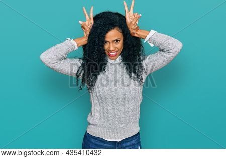 Middle age african american woman wearing casual clothes posing funny and crazy with fingers on head as bunny ears, smiling cheerful