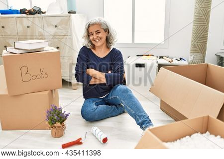Middle age woman with grey hair sitting on the floor at new home happy face smiling with crossed arms looking at the camera. positive person.