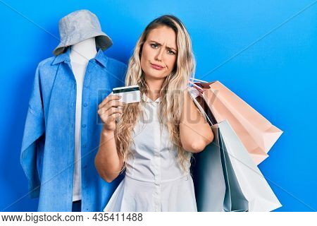Beautiful young blonde woman holding shopping bags and credit card skeptic and nervous, frowning upset because of problem. negative person.