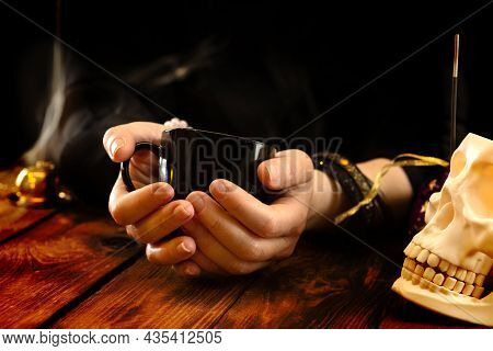 Fortune Teller Or Oracle With A Black Cup In Hand For Fortune Telling On The Coffee Grounds. Psychic