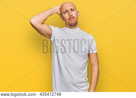 Bald man with beard wearing casual white t shirt confuse and wonder about question. uncertain with doubt, thinking with hand on head. pensive concept.