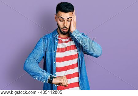 Young hispanic man with beard wearing casual denim jacket looking at the watch time worried, afraid of getting late