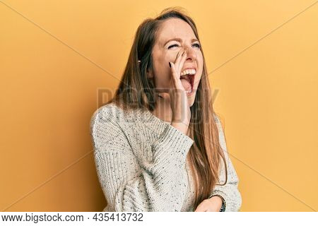 Young blonde woman wearing casual winter sweater shouting and screaming loud to side with hand on mouth. communication concept.