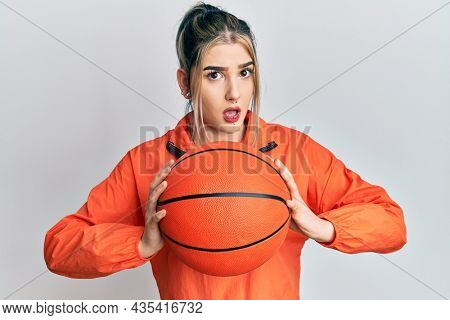 Young modern girl holding basketball ball in shock face, looking skeptical and sarcastic, surprised with open mouth