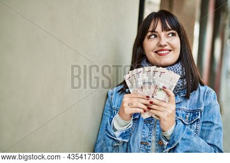 Young brunette woman holding arabia saudi riyal banknotes leaning on the wall