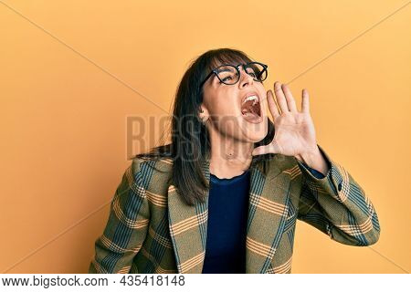 Young hispanic woman wearing business style and glasses shouting and screaming loud to side with hand on mouth. communication concept.