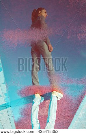 Reflection Photo Of Woman In A Puddle Of Water. Woman Stand Along Walkway And Reflected In Puddle