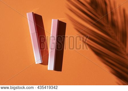 Lip Gloss In A Pink-to-white Gradient Case With Palm Leaves Shadow. Top View On Orange Background. B