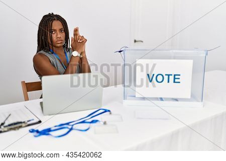 Young african american woman working at political election sitting by ballot holding symbolic gun with hand gesture, playing killing shooting weapons, angry face