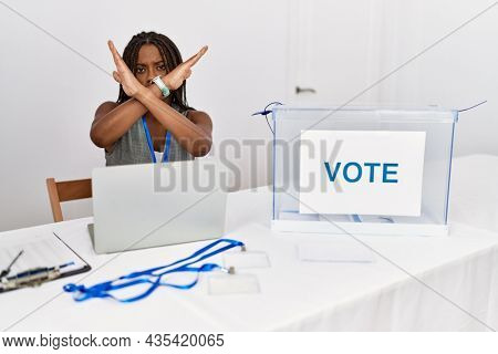 Young african american woman working at political election sitting by ballot rejection expression crossing arms doing negative sign, angry face