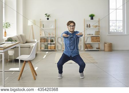 Young Active And Energetic Businessman Squatting Doing Sports Training In His Home Office.