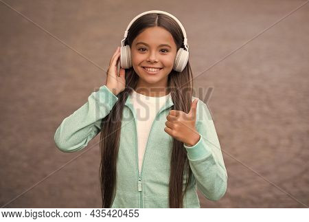 Happy Smiling Child Enjoys Listens To Music In Headphones. Kid Listen Song Outdoor. Walking With Fav
