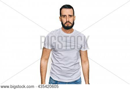 Young man with beard wearing casual white t shirt depressed and worry for distress, crying angry and afraid. sad expression.