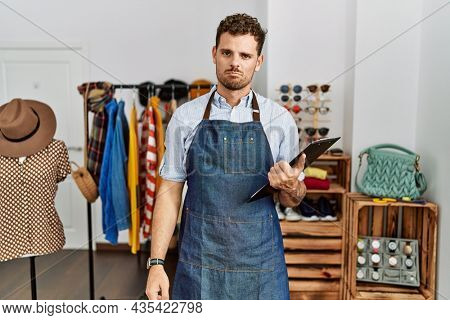 Handsome young man working as manager at retail boutique depressed and worry for distress, crying angry and afraid. sad expression.