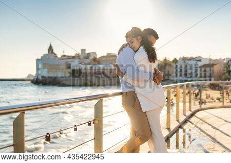 Side View Of Delicate Hispanic Couple Hugging While Standing Near Railing On Promenade Against Sea O