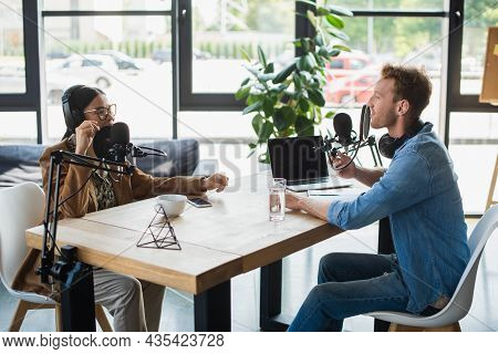 Interracial Radio Hosts Recording Podcast Near Gadgets And Drinks In Studio
