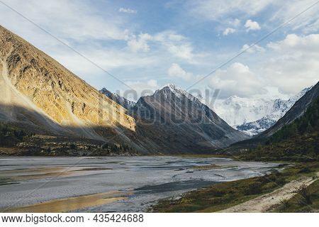 Scenic Landscape With Footpath Along Water Streams In Valley In Autumn Colors With View To Snowy Mou