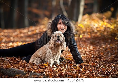 Girl and cocker spaniel in the autumn forest. Focus mainly on the dog poster