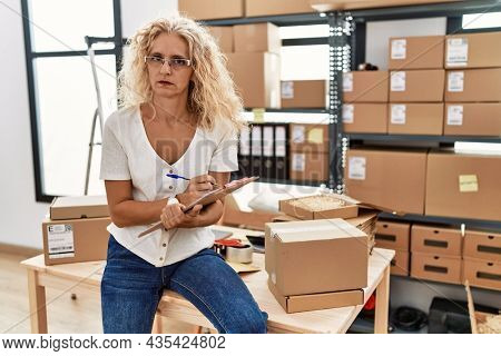 Middle age blonde woman working at small business ecommerce thinking attitude and sober expression looking self confident