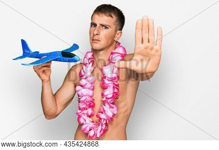 Young blond man wearing swimsuit and hawaiian lei holding airplane toy with open hand doing stop sign with serious and confident expression, defense gesture