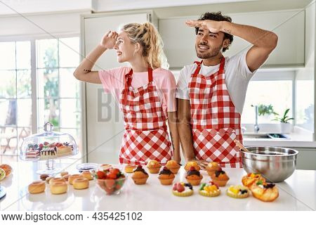 Couple of wife and husband cooking pastries at the kitchen very happy and smiling looking far away with hand over head. searching concept.