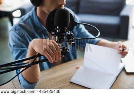 Partial View Of Radio Host In Wireless Headphones Touching Microphone Stand In Studio