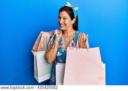 Young latin woman holding shopping bags winking looking at the camera with sexy expression, cheerful and happy face.