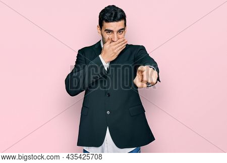 Handsome hispanic man wearing business clothes laughing at you, pointing finger to the camera with hand over mouth, shame expression