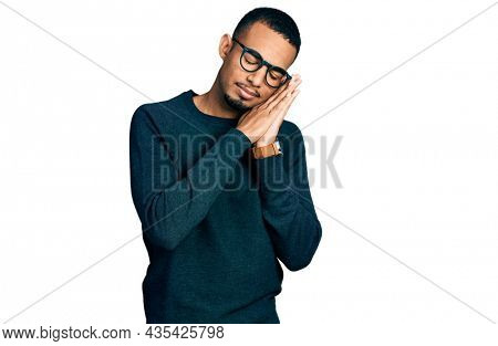 Young african american man wearing casual clothes and glasses sleeping tired dreaming and posing with hands together while smiling with closed eyes.