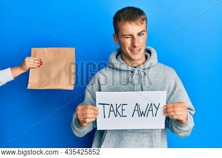 Young caucasian man holding take away banner reciving delivery paper bag winking looking at the camera with sexy expression, cheerful and happy face.