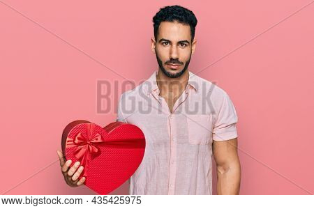 Hispanic man with beard holding valentine gift thinking attitude and sober expression looking self confident